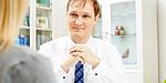 Dr. Samusch sitzt lächelnd an seinem Schreibtisch