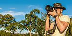 Mann mit Kamera und Safarihut macht Foto