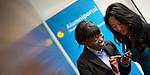 Zwei Frauen vor dem Smartphone, im HIntergrund das Alumniportal-Logo